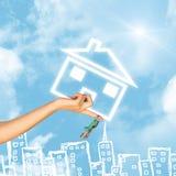 Het huispictogram en sleutel van de handholding Achtergrond van hemel Stock Foto