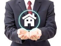 Het huispictogram van de zakenmanholding stock foto
