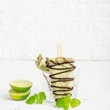 Het huisroomijs van de muntchocolade met donker dik chocoladesuikerglazuur op een lichte achtergrond in een glas met ijs Selectie Stock Foto's