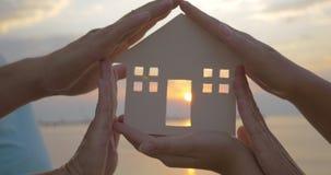 Het Huissilhouet van de handenholding tegen Zon stock footage