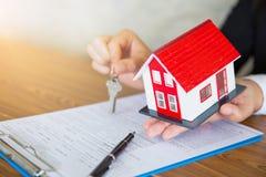 Het huissleutel van de makelaar in onroerend goedholding tot zijn cli?nt na het ondertekenen van contractovereenkomst in bureau,  stock foto's