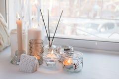 Het huisstilleven in het binnenland met inzameling van kaarsstok en het aroma plakken, op de vensterbank, een comfortabel huisdec stock afbeeldingen