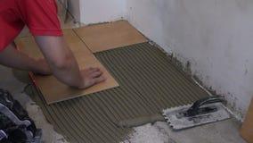 Het huisverbetering manusje van alles die tegel op vloer leggen Gezoem binnen Stock Afbeeldingen