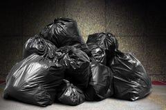 Het huisvuil is de stortplaats van stapelpartijen, velen het zwarte afval van huisvuil plastic zakken bij concrete muur, verontre stock afbeelding