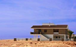 Het huiszitting van het strand op het zand stock foto