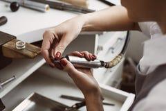 Het hulpmiddel van de juwelier Handen van vrouwelijke juwelier die de hulpmiddelen voor het werk voorbereiden op haar juwelenwork stock foto