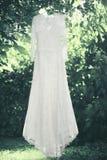 Het huwelijks witte kleding van het huwelijks het elegante kant hangen op een hanger onder boom royalty-vrije stock afbeelding