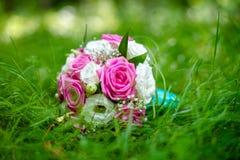 Het huwelijksboeket ligt op het gras Stock Fotografie