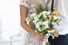 Het huwelijksboeket van de bruidholding Sluit omhoog Stock Foto's