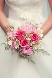 Het huwelijksboeket van de bruidholding van rozen stock foto's