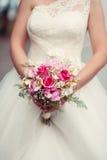 Het huwelijksboeket van de bruidholding van rozen stock afbeelding