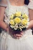 Het huwelijksboeket van de bruidholding van rozen stock fotografie