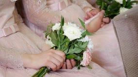 Het huwelijksboeket van de bruidsmeisjeholding tegen kleding stock video