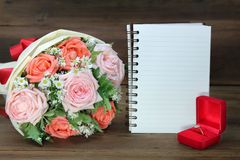 Het huwelijksboeket van roze en oranje rozen, de Trouwring en een wit boeken voor exemplaarruimte op houten achtergrond stock foto