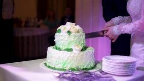 Het huwelijkscake van de bruidenbesnoeiing Een bruid en een bruidegom snijden hun huwelijkscake Handen van bruid en bruidegombesn stock footage