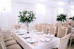 Het huwelijksdecor, toebehoren, orchidee?n, rozen, eucalyptus, een boeket in een restaurant, zit lijst het plaatsen voor royalty-vrije stock foto