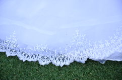 Het huwelijkskleding van het zoom witte kant op groen gras Stock Afbeelding