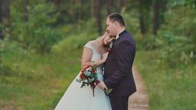 Het huwelijkspaar in het bos de bruid legde haar hoofd op de bruidegom` s schouder Een het raken ogenblik voor een huwelijksdag stock video