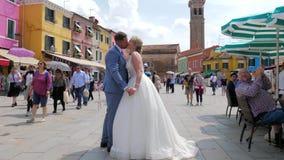 Het huwelijkspaar, de gelukkige bruidegom en de bruid kussen elkaar op de straat op de achtergrond van blije toeristen die toejui stock footage