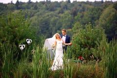 Het huwelijkspaar in liefde op huwelijksdag de bruidegom houdt de bruid in haar wapens dichtbij mooi meer in bos selectieve nadru royalty-vrije stock afbeeldingen