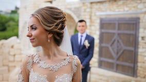 Het huwelijkspaar loopt dichtbij het steenkasteel en de mooie poort Mooi jong enkel gehuwd paar Bruid en bruidegom stock footage