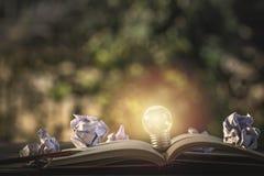 Het idee van het concept Het kweken van gloeilamp op uitstekend boek met verfrommeld p stock afbeelding