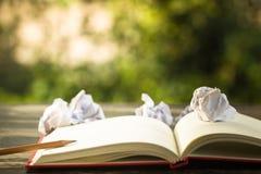 Het idee van het concept Open uitstekend boek met verfrommelde documenten bal en pe stock afbeeldingen