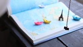 Het idee van de vakantieontwerper toerisme Document boten op de kaart en de Toren van Eiffel stock video