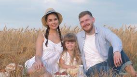 Het idyllische familieportret, gelukkig jong paar zit dicht bij hun kindmeisje en kijkt aan elkaar die in openlucht glimlachen stock videobeelden