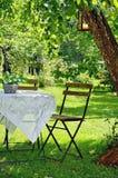Het idyllische plaatsen van een lijst en een houten stoel stock foto's