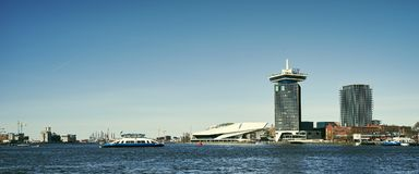 Het IJ, o rio de Amsterdão IJ com balsa, museu do filme do olho e ADAM Tower imagem de stock royalty free