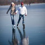 Het ijs dat van het paar op een vijver schaatst stock foto's
