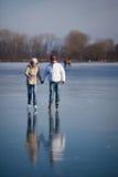 Het ijs dat van het paar in openlucht op een vijver schaatst Stock Afbeelding