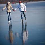 Het ijs dat van het paar in openlucht op een vijver schaatst Stock Fotografie