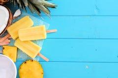 Het ijs van de ananaskokosnoot knalt, hoogste menings zijgrens over blauw hout royalty-vrije stock afbeelding
