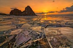 Het ijs van Meer Baikal bij de rots Shamanka, door de het plaatsen zon wordt verlicht die Stock Fotografie