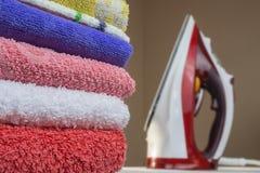Het ijzer en de handdoeken sluiten omhoog Het strijken van schoon linnen stock fotografie