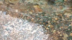 Het ijzige water wast stenen stock video