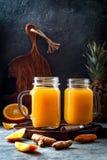 Het immune opvoeren, anti ontstekingssmoothie met sinaasappel, ananas, kurkuma Het sapdrank van de Detoxochtend stock foto's
