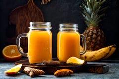 Het immune opvoeren, anti ontstekingssmoothie met sinaasappel, ananas, kurkuma Het sapdrank van de Detoxochtend stock foto