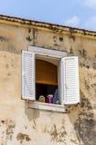 Het inblikken in glaskruiken op het oude middeleeuwse venster van de de bouwvoorgevel stock fotografie