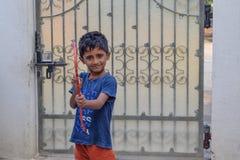 Het Indische jong geitje spelen met zijn boog en pijl in zijn schoolvakantie royalty-vrije stock foto's