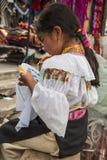 Het Indische meisje in nationale kleren verkoopt de producten van haar weavin stock foto