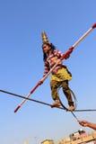 Het Indische meisje voert straatacrobatiek door de kabel uit te lopen Stock Afbeeldingen