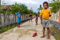 Het Indonesische jongen spelen in de straat Stock Foto's