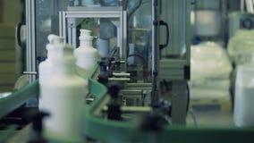 Het industriële mechanisme snijdt halzen van plastic containers af stock video