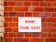 Het informatieteken op rode bakstenen muur voorzichtig zijn dalende leien royalty-vrije stock foto
