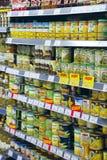 Het ingeblikte voedsel op supermarkt schort ananassen, groene erwten, olijven op Stock Fotografie