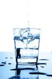 Het inschenken van het water aan glas met ijsblokjes Royalty-vrije Stock Foto's