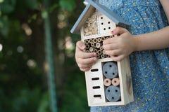 Het insecthotel van de meisjesholding royalty-vrije stock foto's